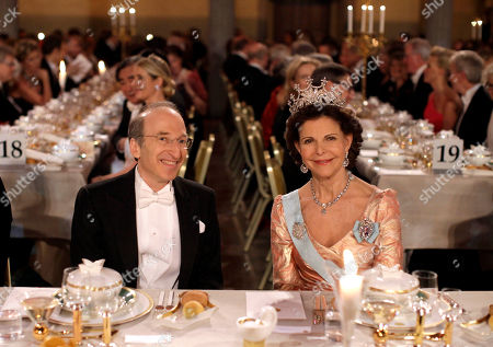 The 2011 Nobel Prize Laureate for Physics Professor Saul Perlmutter of the U.S., left, and Sweden's Queen Silvia smile for photographers at the start of the 2011 Nobel Prize Banquet at the Town Hall in Stockholm