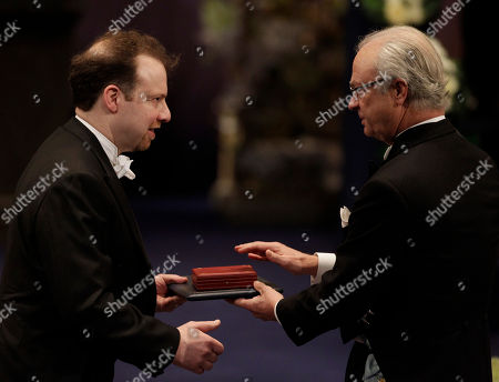 Stock Photo of The 2011 Nobel Prize Laureate for Physics Professor Adam G. Riess from the U.S. receives his Nobel Prize from Sweden's King Carl XVI Gustaf, right, during the Nobel Prize award ceremony at the Stockholm Concert Hall in Stockholm