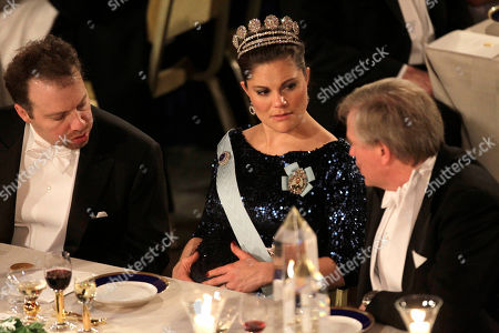 Stock Photo of The 2011 Nobel Prize Laureates for Physics Professor Adam G. Riess from the U.S., left, and Dr. Brian P. Schmidt from Australia, right, speak with Swedish Crown Princess Victoria during the 2011 Nobel Prize Banquet at the Town Hall in Stockholm