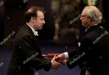 Stock Image of The 2011 Nobel Prize Laureate for Physics Professor Adam G. Riess from the U.S. receives his Nobel Prize from Sweden's King Carl XVI Gustaf, right, during the Nobel Prize award ceremony at the Stockholm Concert Hall in Stockholm
