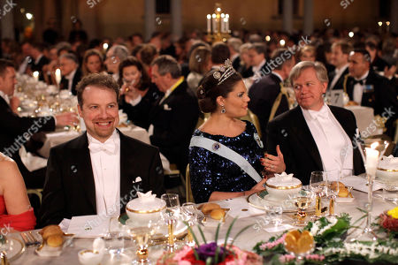 The 2011 Nobel Prize Laureates for Physics Professor Adam G. Riess from the U.S., left, and Dr. Brian P. Schmidt, right, from Australia flank Victoria, Crown Princess of Sweden at the start of the 2011 Nobel Prize Banquet at the Town Hall in Stockholm