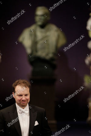 The 2011 Nobel Prize Laureate for Physics Professor Adam G. Riess from the U.S. smiles after receiving his Nobel Prize from Sweden's King Carl XVI Gustaf during the Nobel Prize award ceremony at the Stockholm Concert Hall in Stockholm