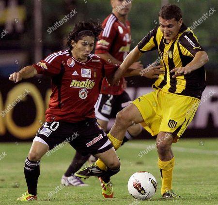 Caracas's Jesus Meza, left, and Uruguay's Penarol Rodrigo Mora compete for the ball during a Copa Libertadores soccer match in Caracas, Venezuela