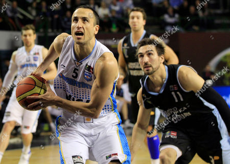 Argentina's Emanuel Ginobili, left, goes for a shot chased by Uruguay's Martin Osimani, right, during a FIBA Americas Championship basketball game in Mar del Plata, Argentina, . The top two finishers of the tournament get an automatic berth in the 2012 London Olympics and the next three advance to the last-chance Olympic qualifier to be held in July 2012