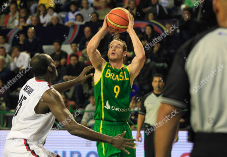 Brazil's Marcelo Huertas, center, prepares to shoot over Canada's Joel Anthony during a FIBA Americas Championship basketball game in Mar del Plata, Argentina, . The top two finishers of the tournament get an automatic berth in the 2012 London Olympics and the next three advance to the last-chance Olympic qualifier to be held in July 2012