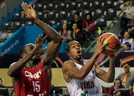 Venezuela's David Cubillan, right, aims for the basket next to Canada's Joel Anthony during a FIBA Americas Championship basketball game in Mar del Plata, Argentina, . The top two finishers of the tournament get an automatic berth in the 2012 London Olympics and the next three advance to the last-chance Olympic qualifier to be held in July 2012