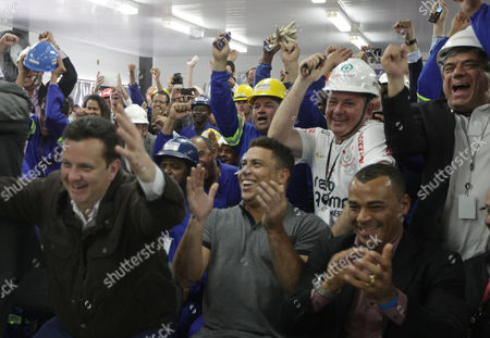 Workers of the new stadium of Brazil's soccer club Corinthians celebrate after the city of Sao Paulo was confirmed by the FIFA as the host of the opening ceremony for the 2014 Soccer World Cup, next to former Brazil's soccer players Ronaldo, front center, Cafu, front right, and Sao Paulo's Mayor Gilberto Kassab, front left, in Sao Paulo, Brazil