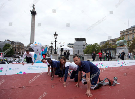 Sebastian Coe, left, the chairman of the London Organising Committee for the 2012 Olympic Games poses for photographs with the London Olympic Games paralympic mascot Mandeville, second from left, and Paralympic athletes, from right, South Africa's Oscar Pistorius, April Holmes and Jerome Singleton from the U.S. and Germany's Heinrich Popow in Trafalgar Square London, . The athletes gathered Thursday to mark international Paralympic Day ahead of the London 2012 Olympic and Paralympic games