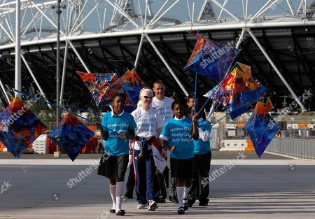 School children with their themed lanterns lead chair of London Olympic Organising Committee, Sebastian Coe, rear right, and Paralympic althletes to arrive for the announcement of plans for the lighting of the Paralympic flame and vision of the Paralympic torch relay at the Olympic Park in London, . Paralympic athletes are swimmer David Roberts, tandem cyclist Aileen McGlynn and former Paralympic 800m Champion Danny Crates