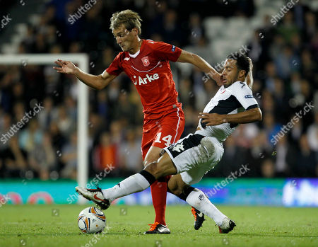 Fulham's Dickson Etuhu, right, competes for the ball with FC Twente's Willem Janssen during their Europa League Group K soccer match at Craven Cottage stadium in London