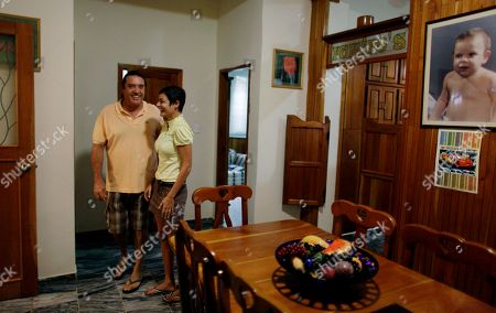 Stock Picture of Tania Duran, right, and her husband Fernando Ramiro stand in their home which they have put on the market in Havana, Cuba, . A new housing law allowing Cubans to freely buy and sell their homes takes effect on Thursday. Listings on a Craigslist-style web site have mushroomed since the law was announced last week. Duran, 34, is confident that she'll find someone on the island with a wallet thick enough to pay $200,000 for her four-bedroom, two-story home, which her family spent years remodeling