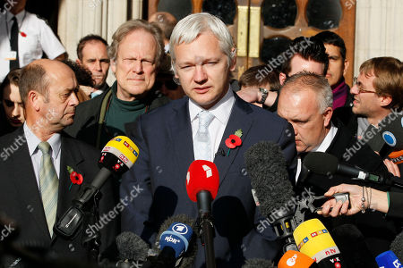 The founder of WikiLeaks Julian Assange, center, gives a statement to the media after his extradition hearing at the High Court in London. Ecuador accused Britain, of threatening to storm its London embassy to arrest Assange after the U.K. issued a stern warning to the South American nation ahead of its decision on an asylum bid by the WikiLeaks founder