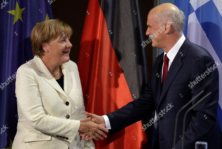 German Chancellor Angela Merkel, left, and the Prime Minister of Greece, Georgios Papandreou, right, shake hands after a statement prior to a dinner at the chancellery in Berlin, Germany