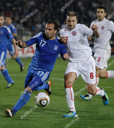 Zurab Khizanishvili of Georgia, right, fights for the ball with Fanis Gekas of Greece during a Euro 2012 Group F qualifying soccer match at the Mikheili Meskhi stadium in Tbilisi