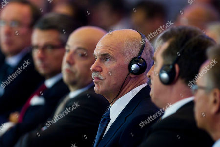 Greek Prime Minister Georgios Papandreou, center, attends an annual conference of the Federation of German Industry (BDI) in Berlin, central Germany, . Papandreou later delivered a speech about Greece and the financial crisis at the meeting, and will meet with Chancellor Angela Merkel in the evening