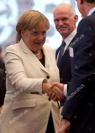 German Chancellor Angela Merkel, left, welcomes Greek Prime Minister Georgios Papandreou as she arrives for a speech at the annual conference of the Federation of German Industry (BDI) in Berlin, central Germany, . Merkel and Papandreou spoke at the conference about their economic policy and the finanial crisis