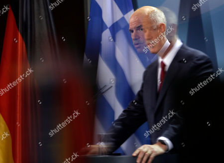 The Prime Minister of Greece, Georgios Papandreou, is seen through glass as he adresses the media during a joint statement with German Chancellor Angela Merkel prior to a dinner at the chancellery in Berlin, Germany
