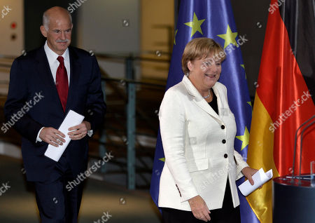 German Chancellor Angela Merkel, right, and the Prime Minister of Greece, Georgios Papandreou, left, arrive for a dinner at the chancellery in Berlin, Germany