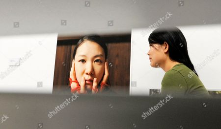 Stock Image of A woman visits the photo installation 'Love -- Hatred' of Park Si-Yeon during the exhibition 'Sparkling Silence. Young Photo Art from Korea' in Erfurt, central Germany, . The exhibition shows photo of art students and graduates of the Fine Art Photography of the Chung-ang University in Seoul, Korea. The artists are students of German photographer Wolfgang Bergmoser, who teaches in Korea. The exhibition started on Oct. 27, 2011 and lasts until Nov. 27, 2011