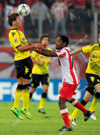 Olympiakos' Jean Makoun, right, pushes Borussia Dortmund's Mario Gotze during their Champions League Group F soccer match in the port of Piraeus, near Athens, on