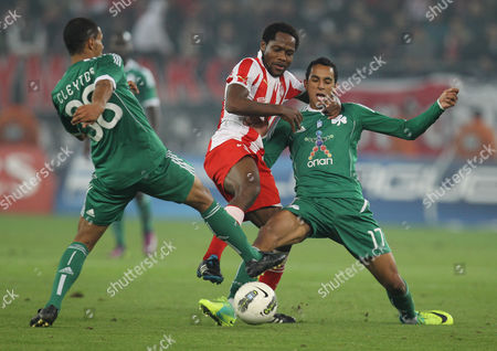Jean Makoun, Zeca, Cleyton Olympiakos' Jean Makoun of Cameroon, center, tries to keep the ball as Panathinaikos Zeca of Portugal, right, and Cleyton of Brazil stop him during their Greek league soccer match at the Karaiskaki stadium in the port of Piraeus, near Athens, . The match ended 1-1