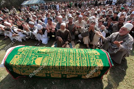 Kashmiri Muslims pray by the coffin of Haji Syed Mohammad Yousuf, a 61-year-old retired teacher and worker of the governing National Conference party in Indian-controlled Kashmir, during his funeral ceremony in Locktipora, some 55 Kilometers (34 miles) south of Srinagar, India, . Yousuf died in police custody Friday after the disputed region's top elected official handed him over to investigators for probing charges that he took money from people promising to get them nominated as lawmakers, according to news reports