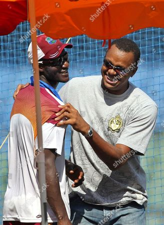 Courtney Walsh, Darren Sammy West Indies former cricket player Courtney Walsh, right, shares a light moment with captain Darren Sammy during a training session ahead of their third test cricket match against India in Mumbai, India, . India won the first two tests
