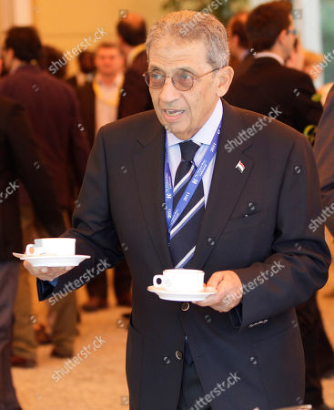 """Amre Moussa, secretary general of the League of the Arab States and candidate for the Egyptian presidential election to be held in autumn 2011, holds two cups of coffee during a break of the """"Intelligence on the World, Europe, and Italy"""" economic forum, at Villa d'Este, in Cernobbio, Como Lake, Italy, . Finance ministers, bankers and economists debate the world's problems at private sessions on the first of a three-day annual forum at this Lake Como resort"""