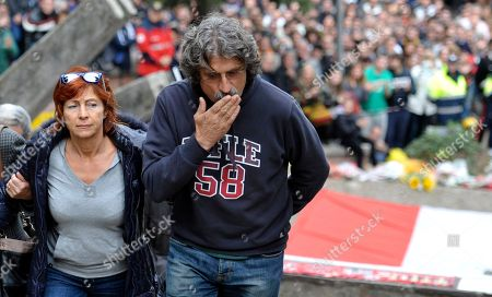 Rossella and Paolo Simoncelli, the parents of late MotoGP rider Marco Simoncelli, arrive at Santa Maria church during his funeral service in his hometown of Coriano, Italy, . Italian sport was in shock after Marco Simoncelli died following a crash at the Malaysian MotoGP motorcycle race. He was 24. Simoncelli - nicknamed Sic or SuperSic - died of chest, head and neck injuries Sunday after he lost control of his Honda at turn 11 four minutes into the race, and swerved across the track, straight into the path of American rider Colin Edwards and Valentino Rossi of Italy