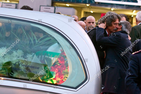 Arrivo all'aeroporto Leonardo Da Vinci di Fiumicino del feretro di Marco Simoncelli Paolo Simoncelli is embraced by Italian Olympic committee president Giovanni Petrucci, right, as the coffin with the body of his son MotoGP rider Marco Simoncelli, left, arrived at the Rome airport, following a fatal accident in the Malaysian Grand Prix. Simoncelli died of chest, head and neck injuries after he lost control of his Honda on Sunday and swerved across the track, straight into the path of American rider Colin Edwards and Italian Valentino Rossi. A public viewing of Simoncelli's body is planned for Wednesday in the city theater of his hometown, Coriano, with the funeral scheduled for Thursday