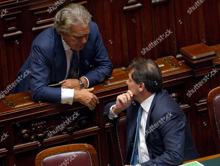 Italian Agriculture minister Saverio Romano, right, talks with lawmaker Denis Verdini prior to a confidence vote on the authorization to his arrest for alleged conections with Mafia mobsters, at the Lower Chamber, in Rome