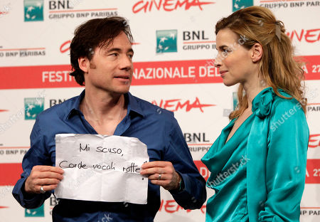 """Thekla Reuten, Michael Herbig German actor Michael Herbig, left, holds a sign reading """"I apologize broken vocal chords"""" as he poses with the actress Thekla Reuten, of the Netherlands, during a photocall to present the movie """"Hotel Lux"""" at the 6th edition of the Rome International Film Festival in Rome"""