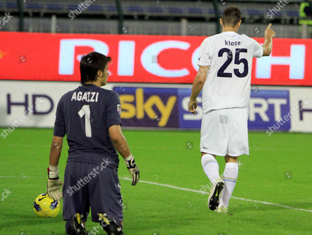 Lazio's Miroslav Klose, of Germany, right, celebrates past Cagliari goalkeeper Michael Agazzi after scoring during a Serie A soccer match between Cagliari and Lazio in Cagliari, Italy