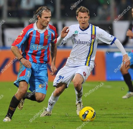 Chievo's French defender Nicholas Sebastien Frey, right, challenges for the ball with Catania's defender Giovanni Marchese during a Serie A soccer match at the Angelo Massimino stadium in Catania, Italy, . Chievo won 2-1