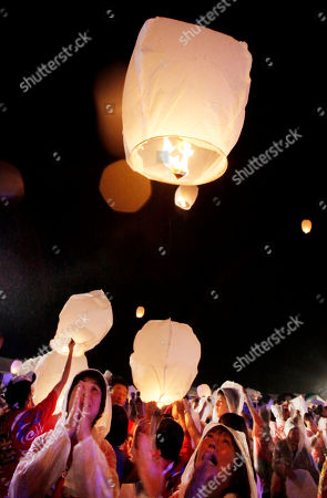 Local residents pray as they release a lantern into the air during a memorial service for the victims of March 11 earthquake and tsunami in Soma, Fukushima prefecture, northeastern Japan, . More than 1,000 mourned the victims in the ceremony organized by Japanese fashion designer Kansai Yamamoto