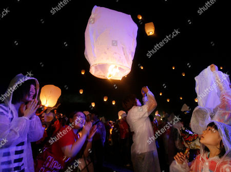 Local residents release a lantern into the air during a memorial service for the victims of March 11 earthquake and tsunami in Soma, Fukushima prefecture, northeastern Japan, . More than 1,000 mourned the victims in the ceremony organized by Japanese fashion designer Kansai Yamamoto