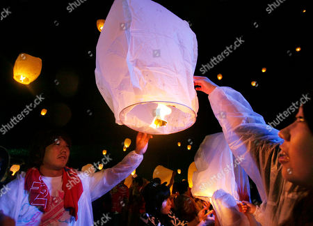 Local residents light up a lantern before launching it into the air during a memorial service for the victims of March 11 earthquake and tsunami in Soma, Fukushima prefecture, northeastern Japan, . More than 1,000 mourned the victims in the ceremony organized by Japanese fashion designer Kansai Yamamoto