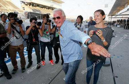 John Button, Jessica Michibata John Button, father of McLaren driver Jenson Button of Britain, left, jokingly pretends to protect Jenson's girl friend Jessica Michibata, right, from the photographers on the Suzuka Circuit at the Japan Formula One Grand Prix in Suzuka