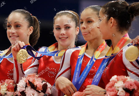 USA's Sabrina Vega, second right, sticks tongue out on the podium along with her teammate as their team won the women's team final at the Artistic Gymnastics World Championships in Tokyo, Japan