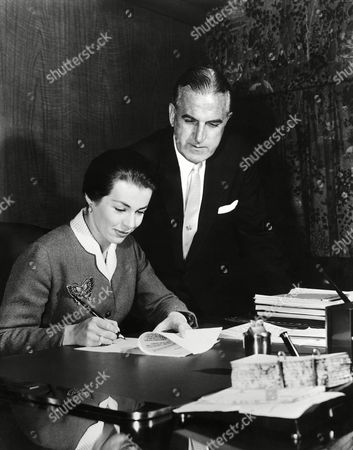 Talented 24-year-old German actress Marianne Koch puts her signature on a long-term Hollywood contract as Universal International President Alfred E. Daff looks on in an undated photo. The signing of this important European star further emphasizes U-I's utilization of world talent as signified by the addition of O.W. Fischer, Cornell Borchers, Rossano Brazzi, John Bentley and Ziva Shapir to the U-I roster of stars