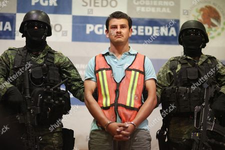 """Juan Gabriel Orozco Favela, alias """"El Gasca"""" alleged member of the Knights Templar drug cartel, is escorted by Mexican Army soldiers as he is presented to the media in Mexico City, . The Defense Department says Orozco Favela was in charge of smuggling drugs through the Michoacan state capital of Morelia for the quasi-religious gang, which is known as a major trafficker of methamphetamine. Officials say Orosco Favela, who was arrested Sunday, was responsible for the deaths of 21 people who were tortured and hanged or drowned and dumped around the outskirts of Morelia in June"""