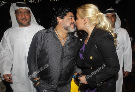 Stock Image of Al Wasl coach Diego Maradona, 2nd left, kisses his partner Veronica Ojeda as they leave after a press conference in Dubai, United Arab Emirates