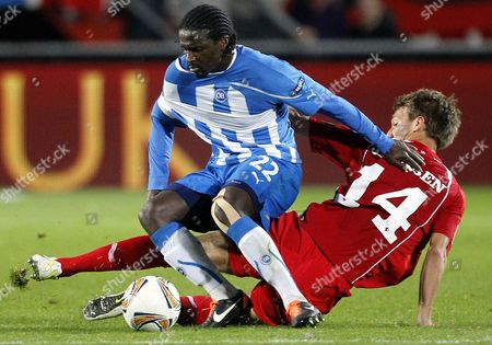 Willem Janssen of FC Twente, right, battles for the ball with Bernard Mendy of Odense BK during their Europa League group K soccer match at the Grolsch Veste stadium in Enschede, The Netherlands