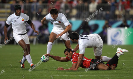 Japan's Ryan Nicholas is tackled by France's Fabrice Estebanez, right, while France's Francois Trinh-Duc, centre, kicks the ball clear during their Rugby World Cup pool C match at North Harbour Stadium in Auckland, New Zealand