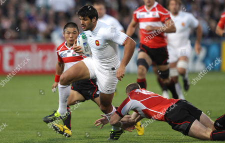 France's Fabrice Estebanez, centre, steps past Japan's Shaun Webb, right, during their Rugby World Cup pool C match at North Harbour Stadium in Auckland, New Zealand