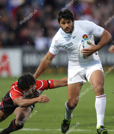 France's Fabrice Estebanez, right, breaks through a tackle by Japan's Fumiaki Tanaka during their Rugby World Cup pool C match at North Harbour Stadium in Auckland, New Zealand