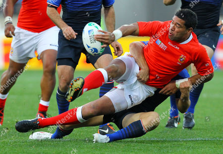 Tonga's Siale Piutau attempts the pass as he is tackled by France's Fabrice Estebanez during their Rugby World Cup game in Wellington, New Zealand