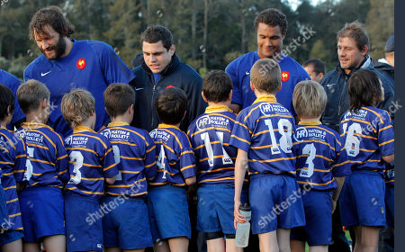 French rugby team players from left Julien Pierre, Raphael Lakafia, Thierry Dusautoir, and Cedric Heymans shake hands with boys from the Takapuna rugby club after a training session, in Auckland, New Zealand, . France will play Canada in their next Rugby World Cup match on Sunday, Sept. 18 in Napier