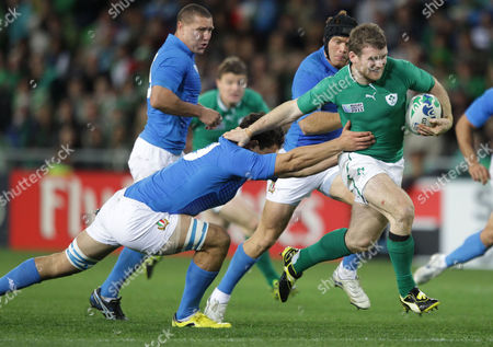 Stock Photo of Ireland's Gordon D'Arcy runs through the tackle by Italy's Fabio Semenzato during their Rugby World Cup match against Italy at Otago Stadium in Dunedin, New Zealand