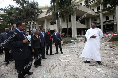 """United Nations Deputy Secretary-General Dr. Asha-Rose Migiro, second left, arrives to inspect the damage of the bombed United Nation's office after a car bombing on Friday in Abuja, Nigeria which killed at least 19 people. Nigeria's president says his government will bring terrorism """"under control"""